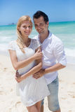 Cheerful couple embracing and posing on the beach on a sunny day Stock Images