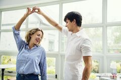Cheerful couple enjoy dancing together in cafe stock image