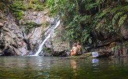 Cheerful couple enjoying river bath by waterfall Royalty Free Stock Image