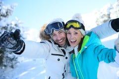 Cheerful couple enjoying their winter holidays on ski slopes Royalty Free Stock Images