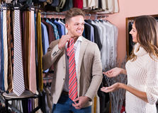 Cheerful couple examining various ties. In men's cloths store Stock Photography