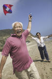 Cheerful Couple Flying Kite On Beach Stock Images
