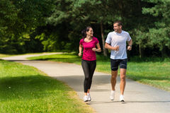 Cheerful couple friends running in park Royalty Free Stock Photo