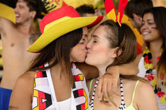 Cheerful couple of German lesbian soccer fans kissing. Cheerful multiethnic couple of German lesbian soccer fans kissing each other celebrating victory Stock Photos