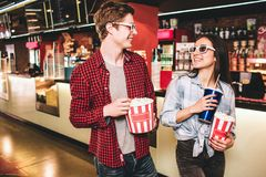 Cheerful couple in glasses are looking to each other and smiling. They are posing. Girl has a cup of coke and a basket. Of popcorn while guy is holding only Royalty Free Stock Image