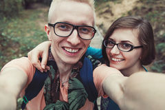 Cheerful couple in glasses makes selfe outdoors Stock Images