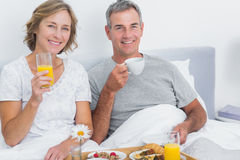 Cheerful couple having breakfast in bed together Royalty Free Stock Photo