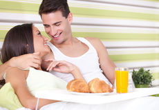 Cheerful couple having breakfast in bed Stock Photography