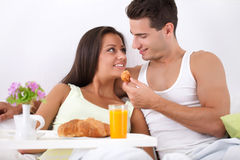 Cheerful couple having breakfast in bed Royalty Free Stock Photo