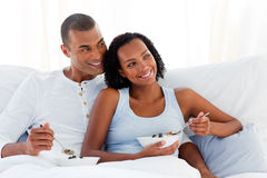 Cheerful couple having breakfast on their bed Royalty Free Stock Photography