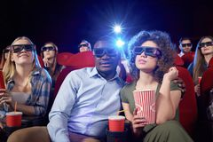 Cheerful couple having date in cinema. Smiling men hugging attractive girlfriend, who keeping popcorn. Cute pair watching interesting comedy and enjoying film royalty free stock photos