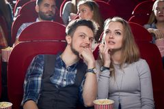 Cheerful couple having date in cinema. Smiling men talking it beautiful blonde girlfriend in gray. Cute pair watching interesting comedy and enjoying film stock images