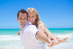 Cheerful couple having fun at the beach on a sunny day Stock Photo