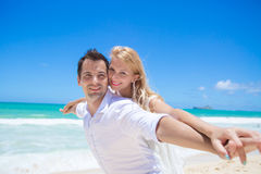 Cheerful couple having fun at the beach on a sunny day Royalty Free Stock Image