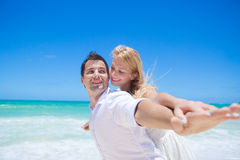 Cheerful couple having fun at the beach on a sunny day Royalty Free Stock Photos