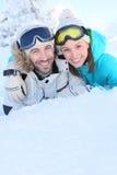 Cheerful couple having fun on ski slopes Stock Photos