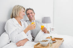 Cheerful couple having orange juice at breakfast in bed Royalty Free Stock Image