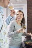 Cheerful couple having wine while cooking in kitchen Royalty Free Stock Photography