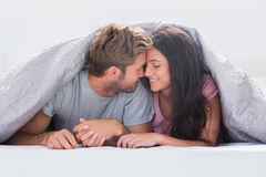 Cheerful couple head against head under the duvet Stock Photography