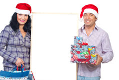 Cheerful couple hold gifts and blank banner royalty free stock photo