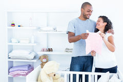 Cheerful couple holding baby clothing Royalty Free Stock Photos