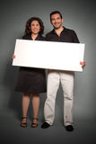 Cheerful couple holding a blank sign Royalty Free Stock Photography