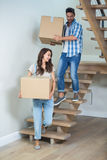 Cheerful couple holding cardboard boxes on steps. At home Stock Photos