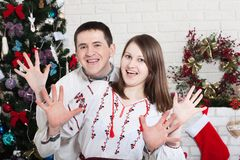 Cheerful couple holding hands enjoying together on Christmas eve. An authentic young couple in ukrainian shirts.. Cheerful couple holding hands enjoying stock image