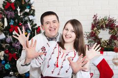 Cheerful couple holding hands enjoying together on Christmas eve. An authentic young couple in ukrainian shirts royalty free stock image