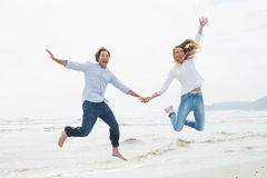Cheerful couple holding hands and jumping at beach Stock Photos