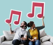 Interracial couple on a couch holding musical notes stock photos