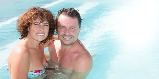 Cheerful couple in home pool in summer Stock Photography