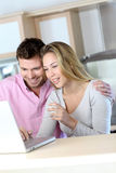 Cheerful couple at home using laptop stock image