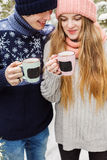Cheerful couple with hot drinks in cups in forest Royalty Free Stock Photography