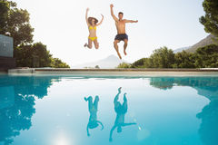 Cheerful couple jumping into swimming pool Royalty Free Stock Image