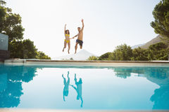 Cheerful couple jumping into swimming pool Stock Photography