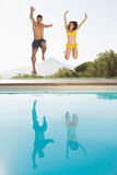 Cheerful couple jumping into swimming pool Royalty Free Stock Photography