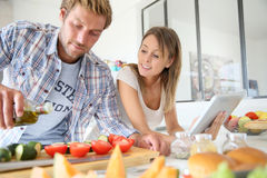 Cheerful couple in the kitchen cooking Stock Photography