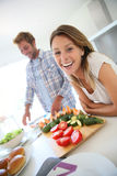 Cheerful couple in the kitchen preparing lunch Stock Photos