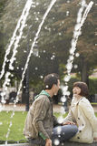 Cheerful Couple Laughing On Fountain Edge Stock Photography