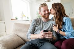 Cheerful young couple laughing watching smart phone Royalty Free Stock Image