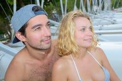 Cheerful couple laying next to sailboats stock photos