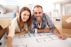 Cheerful couple looking at construction plan Stock Photo