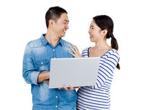 Cheerful couple looking at each other while holding laptop Stock Photography