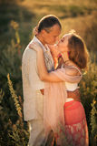 Cheerful couple in love embracing and looking at each other on t. He green spring meadow Stock Photography