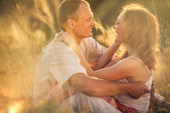 Cheerful couple in love embracing and looking at each other on t. He green spring meadow Royalty Free Stock Image