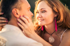 Cheerful couple in love embracing and looking at each other on t. He green spring meadow Royalty Free Stock Photos