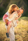 Cheerful couple in love fooling on the green spring meadow. Girl Stock Photos