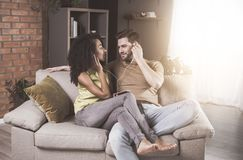 Cheerful couple in love is listening to music at home. My sweetheart. Young enamored husband is sitting on cozy couch with his gorgeous wife. They are enjoying Stock Images