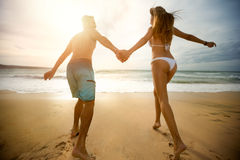 Cheerful couple in love run on the beach Royalty Free Stock Photos